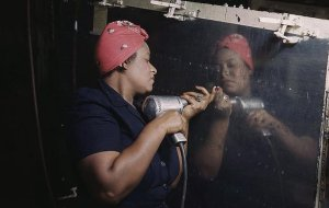 WWII color image of black woman setting rivets in aircraft section