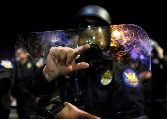 Officer in riot gear making white power sign